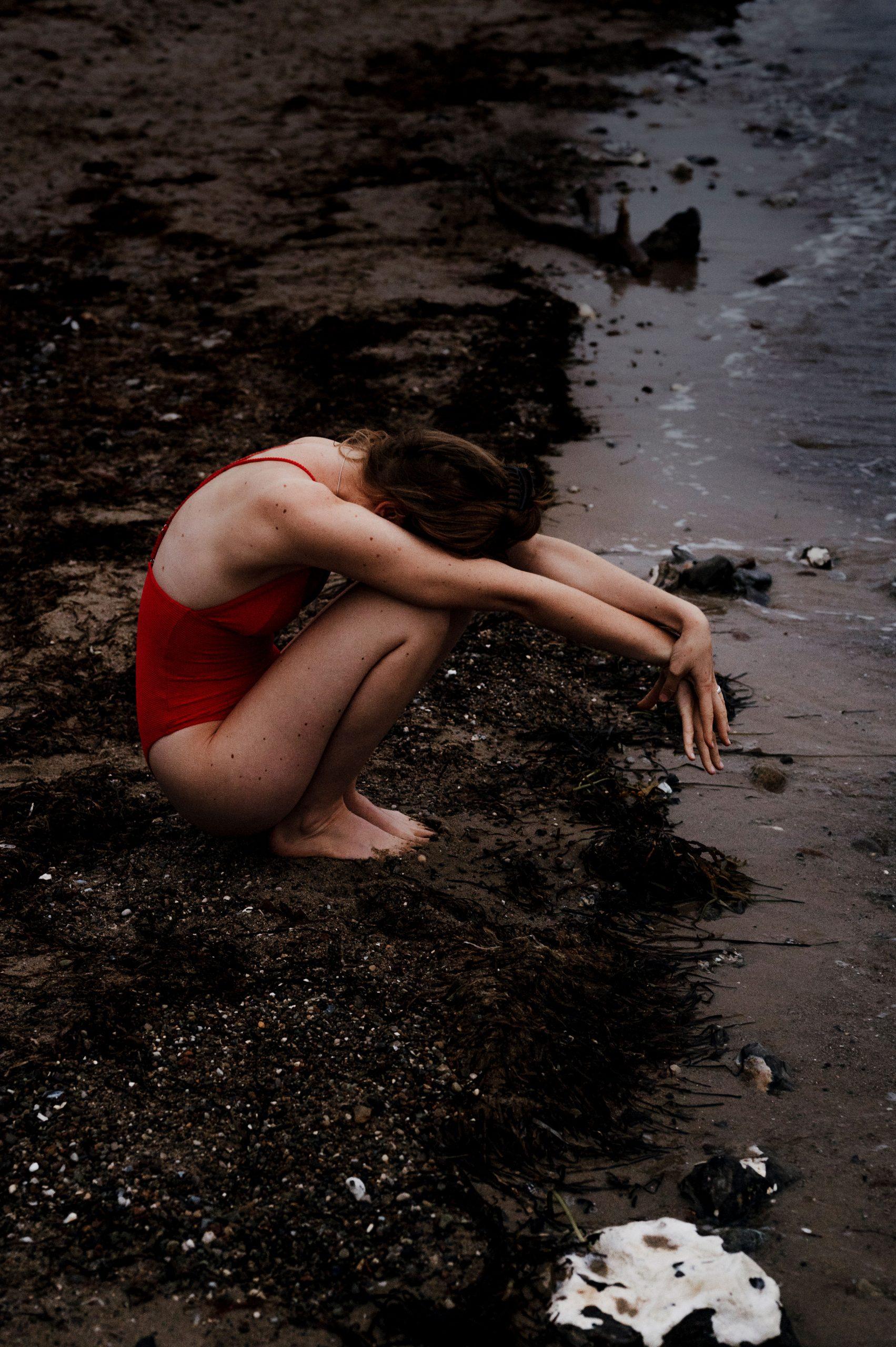 Eine Frau versteckt sich am Meer.